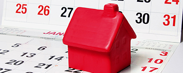 Red plastic toy house on a calendar