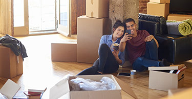 Couple on floor with moving boxes