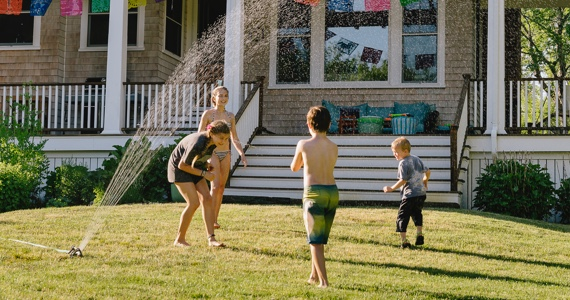 Children play in a sprinkler on a lawn