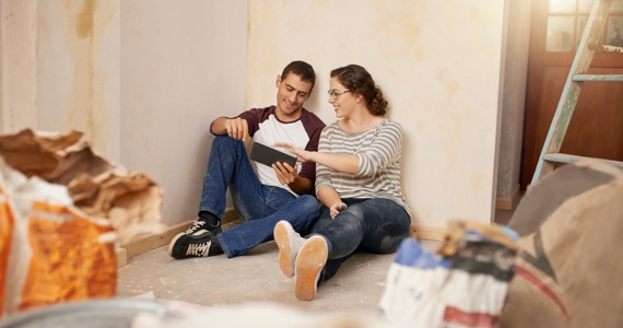 Young couple sitting on the floor in a house under construction